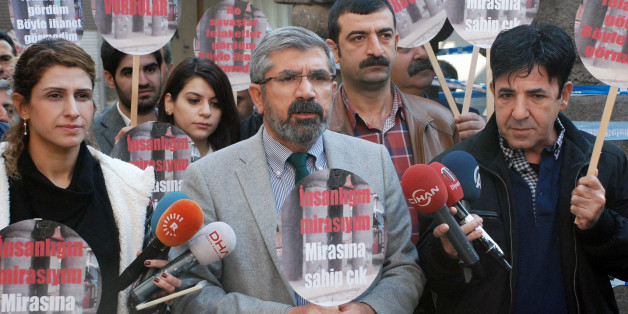 "Tahir Elci, the head of Diyarbakir Bar Association, speaks to the media shortly before being killed in Diyarbakir, Turkey, Saturday, Nov. 28, 2015. Elci, a prominent lawyer, who faced a prison term on charges of supporting Turkey's Kurdish rebels, has been killed in an attack in Diyarbakir. Elci was shot on Saturday while he was making a press statement in front of a historical mosques damaged during fightings between Kurdish rebels and security forces. Elci holds a placard that reads: "" Let's p"