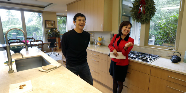 Janie Lee, right, a residential specialist with John L. Scott Real Estate, shares a laugh in the kitchen of a home for sale to she was showing to her client, Hongbin Wei, of Beijing, China, Thursday, Dec. 18, 2014, in Medina, Wash., near Seattle. Real estate agents such as Lee are taking note of growing connections linking China and Washington state, which ranks second to California in real estate sales to Chinese buyers. (AP Photo/Ted S. Warren)