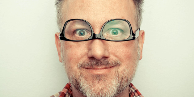 Man wearing glasses upside down, making goofy face. Short hair and grey goatee.