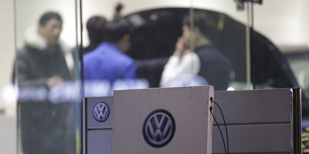 Customers look at a Volkswagen's vehicle at a dealership in Seoul, South Korea,Thursday, Nov. 26, 2015. South Korea said Thursday it fined Volkswagen $12.3 million and ordered recalls of 125,522 diesel vehicles after the government found their emissions tests were rigged. (AP Photo/Ahn Young-joon)