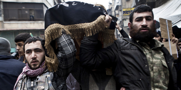 Syrian rebels carry the body of a fallen comrade in Aleppo, Syria, Friday, Dec. 21, 2012.(AP Photo/Virginie Nguyen Hoang)