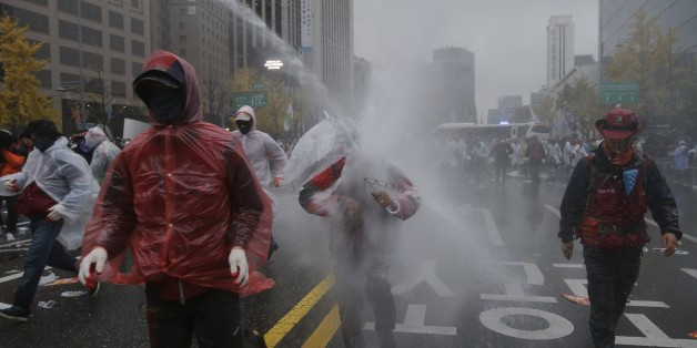 South Korean riot police officers spray water cannons to try to break up protesters who tried to march to the Presidential House after a rally against government policy in Seoul, South Korea, Saturday, Nov. 14, 2015. Police fired tear gas and water cannons Saturday as they clashed with anti-government demonstrators who marched through Seoul in what was believed to be the largest protest in South Korea's capital in more than seven years.(AP Photo/Ahn Young-joon)