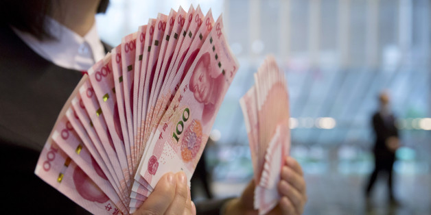 """A staff member displays the new version of the 100-yuan RMB banknotes for photographers at the Bank of China Tower in Hong Kong, Thursday, Nov. 12, 2015. China released Thursday a new version of the 100-yuan bill, which bears a golden """"100"""" and adopts advanced anti-counterfeit technology. The """"100"""" on the new bill appears golden from certain angles. (AP Photo/Kin Cheung)"""