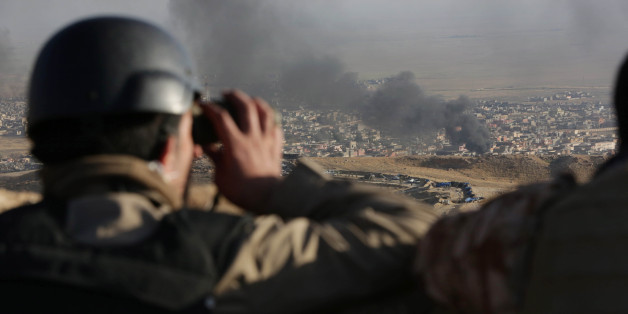 A journalist watches as smoke rises over Sinjar, northern Iraq from oil fires set by Islamic State militants as Kurdish Iraqi fighters, backed by U.S.-led airstrikes, launch a major assault on Thursday, Nov. 12, 2015. The strategic town of Sinjar was overran last year  by the Islamic State group in an onslaught that caused the flight of tens of thousands of Yazidis and first prompted the United States to launch the air campaign against the militants. (AP Photo/Bram Janssen)