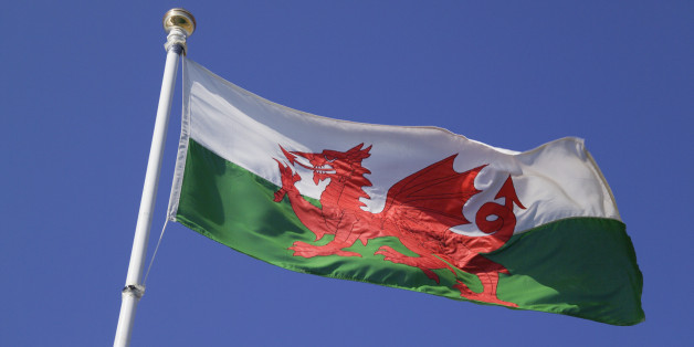 Close up of welsh flag against blue sky, low angle view