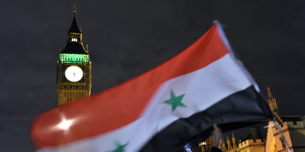 LONDON, ENGLAND - DECEMBER 01:  Protesters hold up a Syrian flag as they take part in a Stop The War Coalition emergency protest on December 1, 2015 in London, England. The emergency protest, which will march past The Conservative and Labour party headquarters, has been organised ahead of tomorrows vote in Parliament on whether the United Kingdom will commence bombing operations over Syria.  (Photo by Ben Pruchnie/Getty Images)