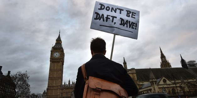 A lone protester opposed to British military action in Syria holds a placard reading 'Don't be daft, Dave!' outside the Houses of Parliament