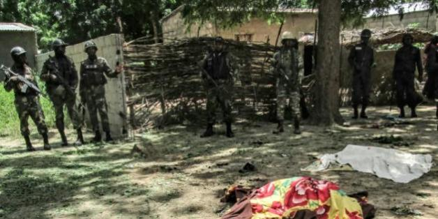 Des membres de la sécurité camerounaise devant la dépouille d'une victime d'un attentat suicide à Kolofata, dans l'extrême nord du Cameroun, le 13 septembre 2015