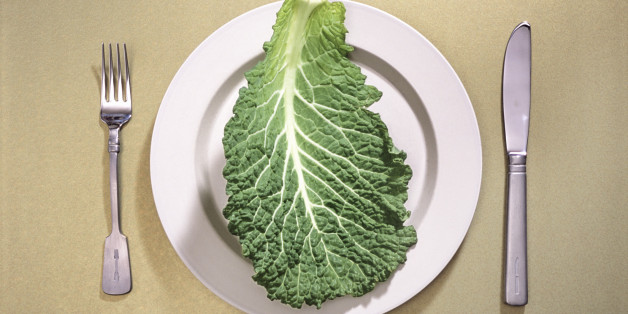 Single leaf of raw kale on ceramic dinner plate