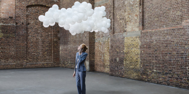 Businesswoman using mobile in empty warehouse with cloud made of balloons above head