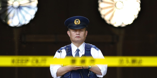 In this Tuesday, Nov. 24, 2015, file photo, a police officer stands guard in front of the south gate of Yasukuni shrine in Tokyo. An explosion on Monday damaged a public restroom at a controversial shrine in Tokyo that honors Japanese war dead, with police suspecting foul play. No one was injured. (AP Photo/Shizuo Kambayashi, File)