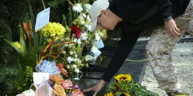 Un touriste fleurit la tombe de Pablo Escobar à Medellin le 2 décembre 2015