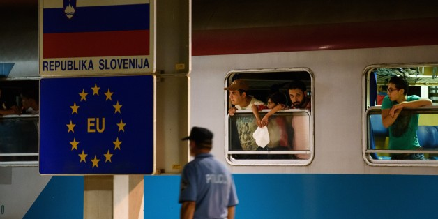 A police officer walks past migrants waiting in a train at the railway station, near the Slovenian-Croatian border in Dobova, Brezice, on September 17, 2015. Slovenia intends to reinforce its border with Croatia ahead of a possible influx of migrants seeking a new route into Europe's borderless Schengen area, the country's police chief said on September 16. Migrants have begun carving a new route into the Schengen area, travelling via Croatia, after neighbouring Hungary, overwhelmed by the refugee traffic, fenced off its own border with Serbia.  AFP PHOTO / JURE MAKOVEC        (Photo credit should read Jure Makovec/AFP/Getty Images)