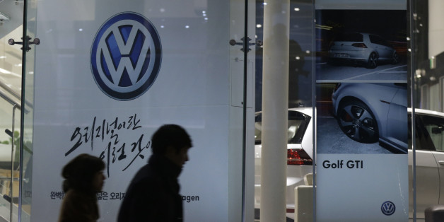 People walk by a logo of Volkswagen at a dealership in Seoul, South Korea, Thursday, Nov. 26, 2015.  South Korea said Thursday it fined Volkswagen $12.3 million and ordered recalls of 125,522 diesel vehicles after the government found their emissions tests were rigged. (AP Photo/Ahn Young-joon)