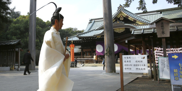 A Shinto priest walks in front of the main shrine during the four-day annual Autumn Festival in the compound of Yasukuni Shrine in Tokyo, Tuesday, Oct. 20, 2015. The shrine honors Japan's war dead, including convicted World War II leaders. (AP Photo/Shizuo Kambayashi)