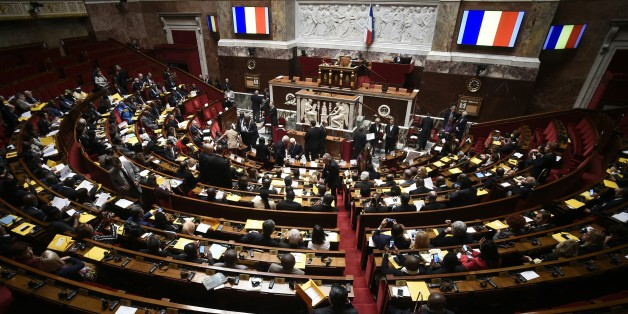 A picture taken on December 5, 2015 shows French flags on screens during a parliamentary meeting on the occasion of the United nations conference on climate change at the French National Assembly in Paris. / AFP / LIONEL BONAVENTURE        (Photo credit should read LIONEL BONAVENTURE/AFP/Getty Images)