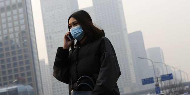 A woman wearing a mask to protect herself from pollutants walks past office buildings shrouded with pollution haze in Beijing, Monday, Dec. 7, 2015. Smog shrouded the capital city Monday after authorities in Beijing issued an orange alert on Saturday. (AP Photo/Andy Wong)