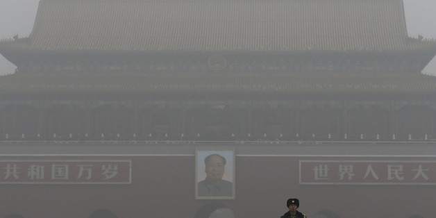 A Chinese paramilitary policeman stands on duty near Tiananmen Gate shrouded with heavy pollution and fog in Beijing, Tuesday, Dec. 1, 2015. Schools in the Chinese capital kept students indoors and parents brought their kids to hospitals with breathing ailments Tuesday as Beijing grappled with extremely severe air pollution for the fifth straight day. (AP Photo/Andy Wong)