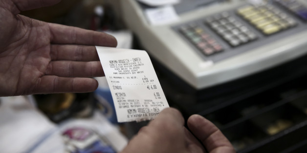In this photo taken Sept. 30, 2015, Yiannis Fragiskos, owner of a souvenir shop, displays a receipt inside his shop at the port of the Greek Aegean island of Naxos. For decades, Greece's Aegean islands enjoyed a value added tax rate 30 percent lower than the rest of the country, to offset increased transportation costs and prevent their dwindling permanent populations from deserting them altogether, but now the islands are losing that benefit as part of creditor-demanded reforms for Greece'