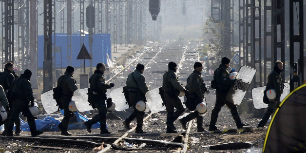 Greek riot police officers walk across railway tracks at Idomeni railway station in northern Greece on the border with Macedonia, photographed from the Macedonian side of the border, near the town of Gevgelija, Wednesday, Dec. 9, 2015. The protest of stranded migrants had severed a key Greek freight train link with northern Europe for three weeks, and also periodically prevented refugees that Macedonia will accept from crossing the border. Some railway services restarted Wednesday after Greek riot police have removed hundreds of protesting migrants from a border crossing to Macedonia. (AP Photo/Boris Grdanoski)