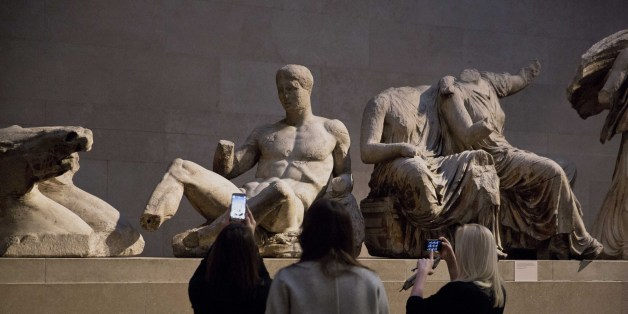 Women take pictures of a marble statue of a naked youth thought to represent Greek god Dionysos, center, from the east pediment of the Parthenon, on display during a media photo opportunity to promote a forthcoming exhibition on the human body in ancient Greek art at the British Museum in London, Thursday, Jan. 8, 2015.  The exhibition, which is due to open on March 26, will feature around 150 objects including some from the museum's permanent Greek collection and other items from international collections.  (AP Photo/Matt Dunham)