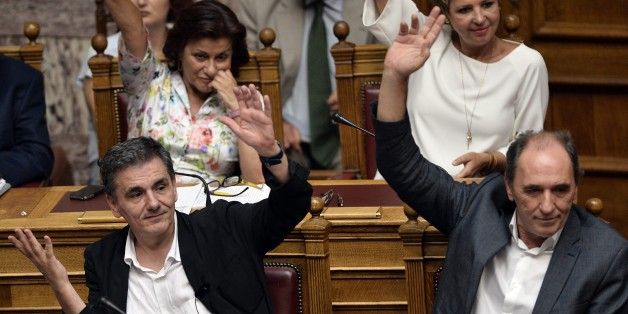Greek Finance Minister Euclid Tsakalotos (L) and Economy Minister Giorgos Stathakis  vote on procedure during a parliamentary debate  in Athens early on August 14, 2015.  Greek lawmakers  held an emergency parliamentary session for a crucial vote on ratifying a hurriedly-concluded bailout deal, but Germany -- Europe's de facto paymaster -- has cast doubt on the agreement.  AFP PHOTO / LOUISA GOULIAMAKI        (Photo credit should read LOUISA GOULIAMAKI/AFP/Getty Images)