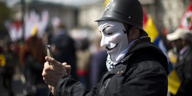 A protester wearing a toy British police helmet and an Anonymous mask takes a picture during a rally at the end of a May Day demonstration march in Trafalgar Square in London, Friday, May 1, 2015. Tens of thousands of workers marked May Day in European cities with a mix of anger and gloom over austerity measures imposed by leaders trying to contain the eurozone's intractable debt crisis. (AP Photo/Matt Dunham)