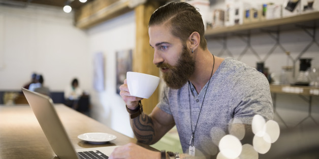 Bearded man drinking coffee at laptop in cafe
