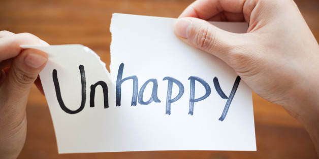 Close-up of hands tearing the word on paper, Unhappy become Happy.