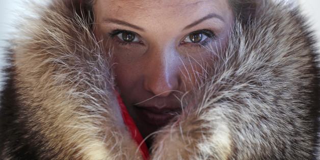 "Pam Paquin poses with an ""accidental fur"" raccoon neck muff she created in Central Massachusetts, Wednesday, Nov. 18, 2015. Paquin's company, Petite Mort, uses roadkill fur harvested from animal carcasses culled with the help of highway departments and animal control officers. (AP Photo/Charles Krupa)"