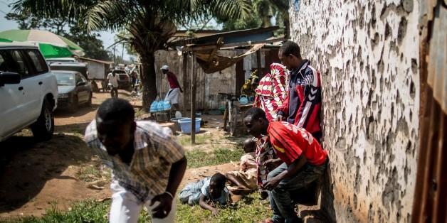 Des hommes se mettent à l'abri pendant que des tirs à l'arme lourde retentissent à Bangui, le 13 décembre 2015