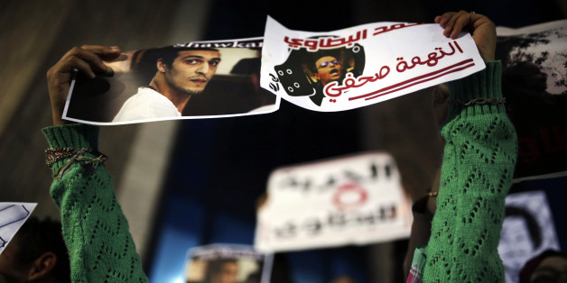 An Egyptian journalist holds posters calling for the release of photojournalists Mohammad al-Batawi, right, and Mahmoud Abou-Zeid, known as Shawkan, in front of the Syndicate of Journalists building in Cairo, Egypt, Wednesday, Dec. 9, 2015. Shawkan was arrested in August 2013 while taking photographs of the government's violent dispersal of a sit-in by supporters of ousted Islamist President Mohammed Morsi and has spent over 800 days locked up without  charges. (AP Photo/Amr Nabil)