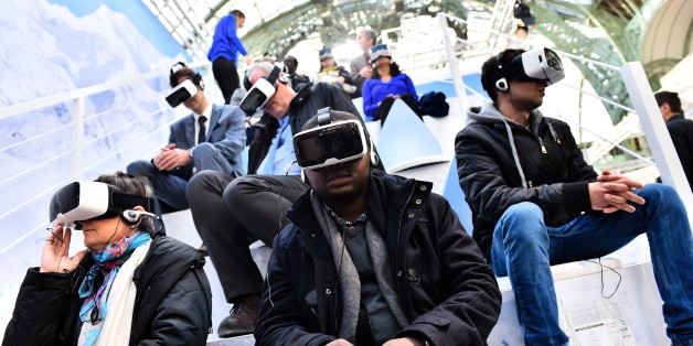 Visitors test virtual reality headsets at the 'Solutions COP21' exhibition at the Grand Palais in Paris on December 4, 2015 on the sidelines of the COP21 United Nations conference on climate change. / AFP / LOIC VENANCE        (Photo credit should read LOIC VENANCE/AFP/Getty Images)