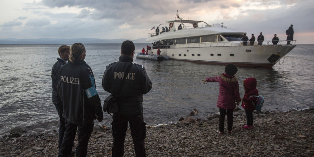 Frontex security personnel watch refugees and migrants disembarking from a yacht on the Greek island of Lesbos, after crossing a part of the Aegean sea from Turkey's coast, early in the morning Saturday, Nov. 21, 2015. Most nations along Europe's refugee corridor, except Greece, abruptly shut their borders Thursday to those not coming from war-torn countries such as Syria, Afghanistan or Iraq, leaving thousands desperately seeking a better life in the continent stranded at Balkan border crossings. (AP Photo/Santi Palacios)