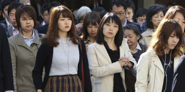 In this Monday, Oct. 26, 2015 photo, commuters cross a street during morning rush hour in Tokyo. The central government exceeded its 30 percent target for hiring of women for career-track positions, raising the rate to 34 percent this year from 24 percent last year, according to the latest Cabinet Office data. Two years after Prime Minister Shinzo Abe made women's advancement a top policy priority, statistics suggest Japan's male-dominated workplaces have evolved slightly, but also hig