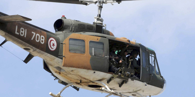 A Tunisian army helicopter flies over the Bardo museum, Wednesday, March 18, 2015 in Tunis, after gunmen opened fire at the Bardo museum in Tunisia's capital. Authorities say scores of people are dead after an attack on a major museum in the Tunisian capital, and some of the gunmen may have escaped. (AP Photo/Ali Ben Salah)