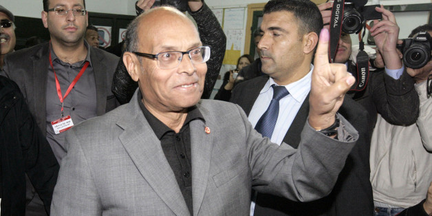 Tunisia's outgoing President, Moncef Marzouki, displays the indelible ink mark on his finger after voting in  Sousse, 120 miles south of Tunis, Tunisia, Sunday, Dec, 21, 2014. Tunisians must decide Sunday between Beji Caid Essebsi, an 88-year-old veteran of previous regimes, and Moncef Marzouki, a 75-year-old human rights activist who is the outgoing interim president. For the third time in just two months, Tunisian voters will head to the polls this weekend, this time to elect a president in a runoff vote that presents a stark choice between the country's past and its Arab Spring revolution. (AP Photo/Slim Abid)