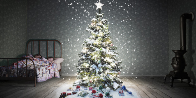 A classic children's bedroom (vintage miniature) with a glowing decorated christmas tree with snow falling.  There a two caucasian sisters in the bed that appear to be under 10 years old or younger.