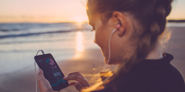 Woman using self tracking app on her smartphone after running at the beach.