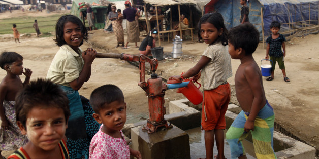 In this photo taken on April 2, 2014, Muslim refugee children gather at a tube-well to fetch water near their tents at Da Paing camp in north of Sittwe, Rakhine State, western Myanmar. Myanmar vowed Wednesday to protect U.N. and humanitarian aid workers seeking to return to the strife-torn state of Rakhine after rampaging Buddhist mobs attacked the workers' homes and offices. (AP Photo/Khin Maung Win)