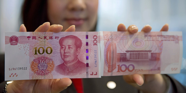 """A staff member displays the new version of the 100-yuan RMB banknotes (US 15.7 dollars) to photographers at the Bank of China Tower in Hong Kong, Thursday, Nov. 12, 2015. China released Thursday a new version of the 100-yuan bill, which bears a golden """"100"""" and adopts advanced anti-counterfeit technology. The """"100"""" on the new bill appears golden from certain angles. (AP Photo/Kin Cheung)"""