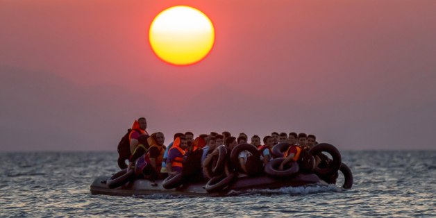 FILE - Migrants on a dinghy arrives at the southeastern island of Kos, Greece, after crossing from Turkey, Thursday, Aug. 13, 2015. Greece has become the main gateway to Europe for tens of thousands of refugees and economic migrants, mainly Syrians fleeing war, as fighting in Libya has made the alternative route from north Africa to Italy increasingly dangerous. (AP Photo/Alexander Zemlianichenko, File)