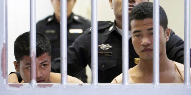 Myanmar migrants Win Zaw Htun, right, and Zaw Lin, left, both 22, are escorted by officials after their guilty verdict at court in Koh Samui, Thailand, Thursday, Dec. 24, 2015. A Thai court on Thursday sentenced the two Myanmar migrants to death for killing British backpackers David Miller, 24, and Hannah Witheridge, 23, on the resort island of Koh Tao last year, a crime that focused global attention on tourist safety and police conduct in the country. (AP Photo/Wason Wanichakorn)