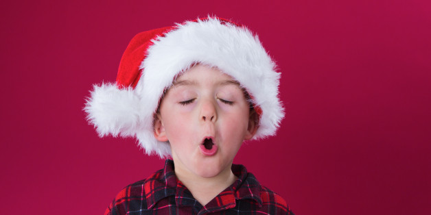 a little boy sings a song for Christmas on red background. They are both wearing Santa hats.