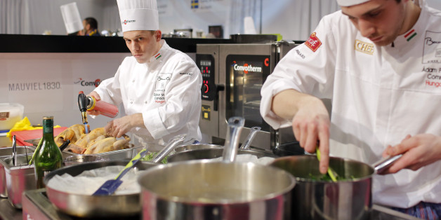 """Gabor Molnar of Hungary, left, prepares food with his assistant Adam Pohner, right, during the """"Bocuse d'Or"""" (Golden Bocuse) trophy, at the 15th World Cuisine contest, in Lyon, central France, Wednesday, Jan. 28, 2015. The contest, a sort of world cup of the cuisine, was started in 1987 by Lyon chef Paul Bocuse to reward young international culinary talents. (AP Photo/Laurent Cipriani)"""