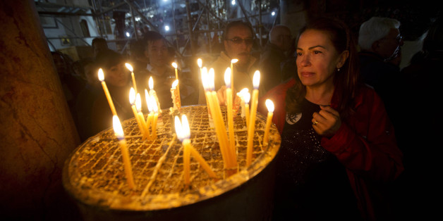 A Christian worshipper lights a candle at the Church of the Nativity, where Christians believe Jesus Christ was born, in the West Bank city of Bethlehem, Wednesday, Dec. 23, 2015. (AP Photo/Majdi Mohammed)