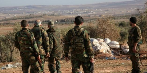 Des forces syriennes pro-gouvernement surveillent une zone près du village de Khan Tuman dans la province d'Alep, le 22 décembre 2015