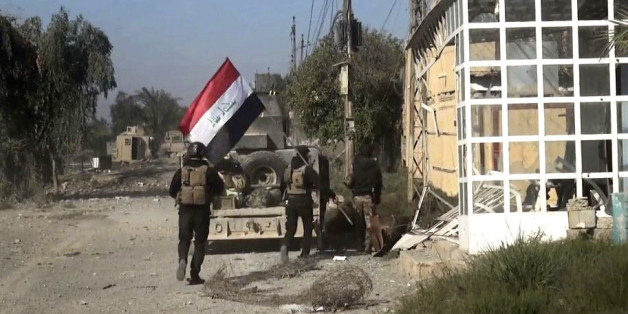 Iraqi security forces hold a national flag as they enter the southern neighborhoods of Ramadi, 70 miles (115 kilometers) west of Baghdad, Iraq, Wednesday, Dec. 23, 2015. Iraqi security forces' advance was slowed by snipers, roadside bombs and booby trapped buildings, military spokesman Brig. Gen. Yahya Rasool, told The Associated Press. Rasool said some of the families that were trapped in Ramadi had managed to flee the city and reached safe areas. (AP Photo)