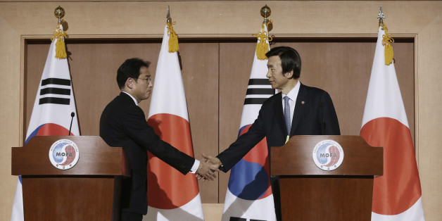 South Korean Foreign Minister Yun Byung-se, right, shakes hands with his Japanese counterpart Fumio Kishida after their joint press conference at Foreign Ministry in Seoul, South Korea, Monday, Dec. 28, 2015. The foreign ministers said they had reached a deal meant to resolve a decades-long impasse over Korean women forced into Japanese military-run brothels during World War II, a potentially dramatic breakthrough between the Northeast Asian neighbors and rivals. (AP Photo/Ahn Young-joon)