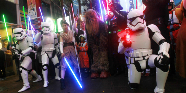 """Fans dressed as Star Wars characters parade outside a movie theater showing """"Star Wars: The Force Awakens"""" Saturday, Dec. 19, 2015, in Taipei, Taiwan. (AP Photo/Chiang Ying-ying)"""